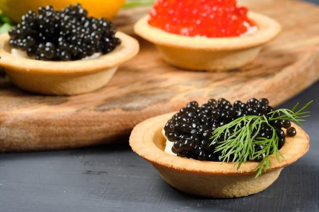 Tortinhas com caviar vermelho e preto em uma placa de madeira com limão e ervas.