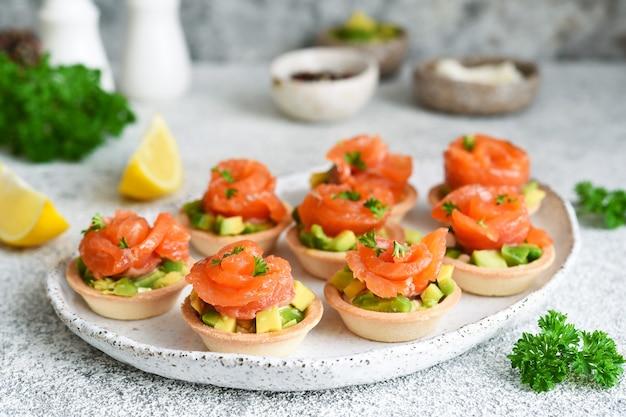 Tortinhas com cream cheese, abacate e salmão. aperitivo de salmão na mesa da cozinha.