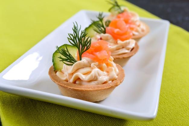 Tortinhas com cream cheese e salmão salgado em um prato branco