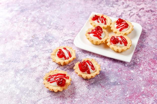 Tortinhas com recheio de chocolate branco e geleia de frutas vermelhas por cima.