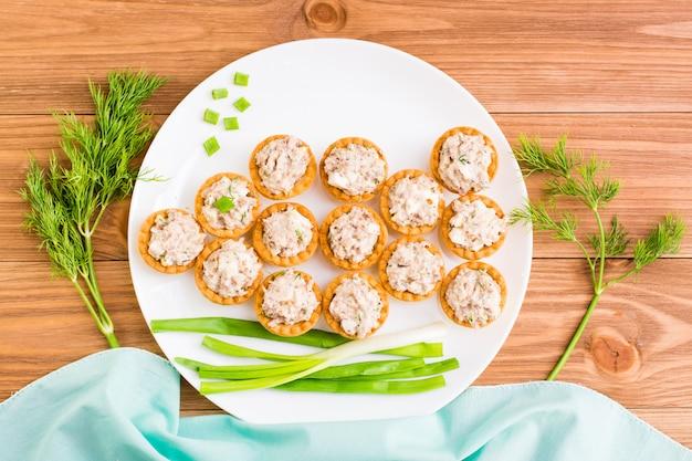 Tortinhas com salada de sauro e ovos são dispostas em um prato em forma de peixe, vista superior