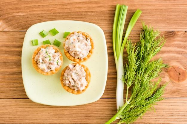Tortinhas com salada em um pires e verduras em uma mesa de madeira