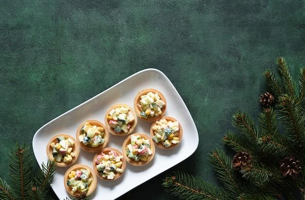 Tortinhas com salada na mesa do ano novo. com salada com palitos de caranguejo