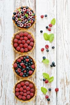Tortinhas de framboesa e mirtilo com ganache de chocolate, frutas frescas e folhas de hortelã, foco seletivo.