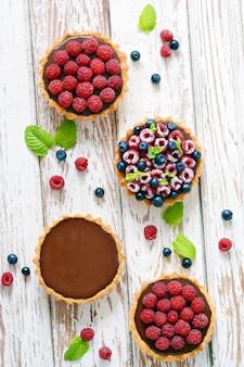 Tortinhas de framboesa e mirtilo com ganache de chocolate, frutas frescas e folhas de hortelã