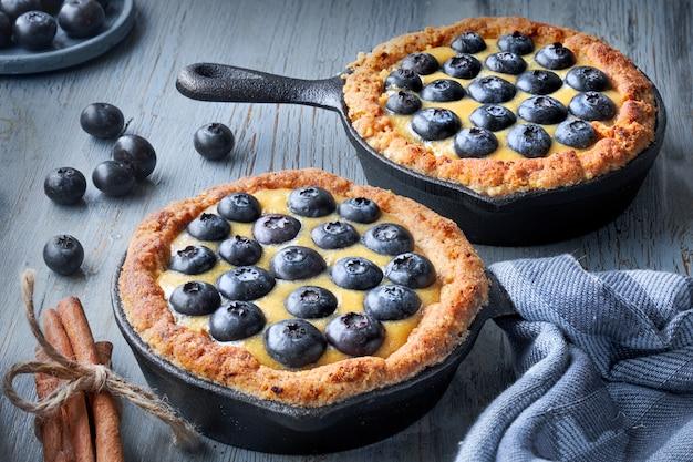 Tortinhas de mirtilo deliciosas com creme de baunilha em madeira rústica cinza