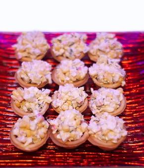 Tortinhas ou mini tortinhas com salada de milho e caranguejo em prato vermelho
