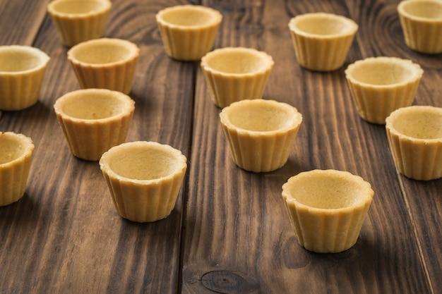 Tortinhas vazias dispostas sobre uma mesa de madeira. produtos de padaria para aperitivos.