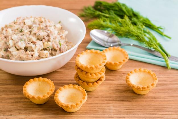 Tortinhas vazias e salada pronta de conservas de peixe e ovos
