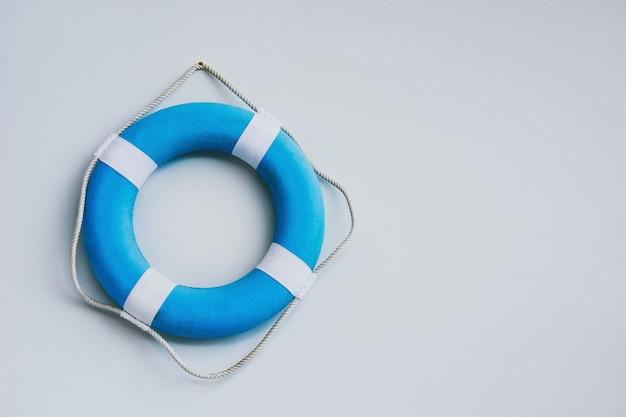 Torus de segurança azul e branco ou lifebuoy pendurado no fundo da parede branca, cópia espaço