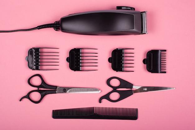 Tosquiadeira e tesoura com pente em um fundo rosa, ferramentas de barbeiro.