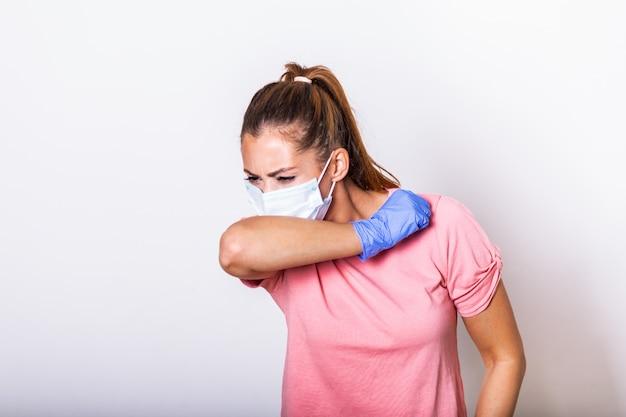Tosse de mulher no cotovelo com proteção de máscara cirúrgica. covid - 19, prevenção de coronavírus
