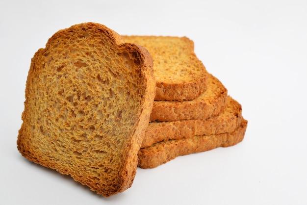 Tostas crocantes ou torradas para uma vida saudável tostas criando um efeito dominó isolado em uma mesa branca - fatias de biscoitos de torradas semelhantes a torradas