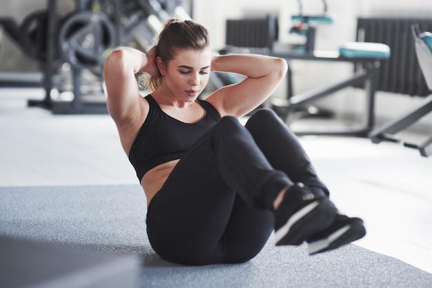 Totalmente concentrado no exercício. foto de uma linda mulher loira na academia no fim de semana
