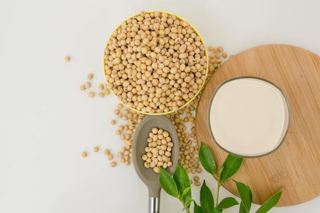 Totalmente feijão de soja na tigela, leite de soja e colher na mesa branca.