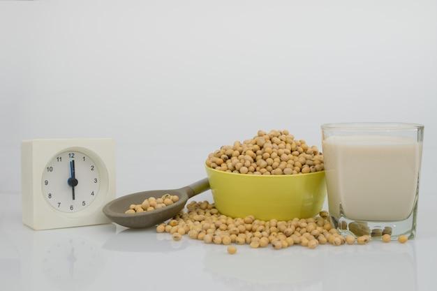 Totalmente grãos de soja na tigela, leite de soja e colher para manhã pausa na mesa branca.
