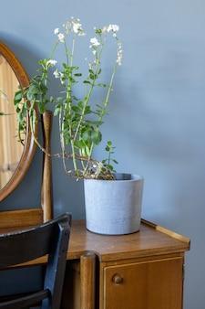 Toucador antigo com moldura de madeira espelho na sala azul com vista lateral para as flores caseiras