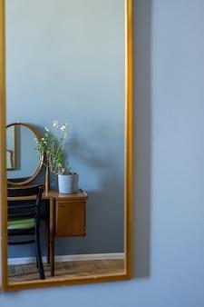 Toucador antigo com moldura de madeira espelho na sala azul com vista lateral para as flores caseiras Foto Premium