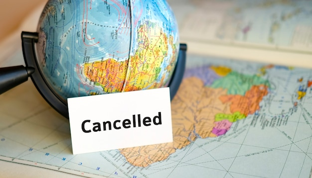 Tour cancelado - texto em uma folha branca no pequeno globo no fundo do mapa do atlas