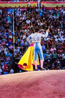 Toureiro fazendo movimentos na frente dos espectadores na arena