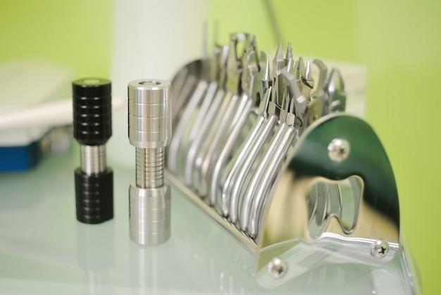 Tourette ortodôntico e pinça odontológica em uma mesa de close-up