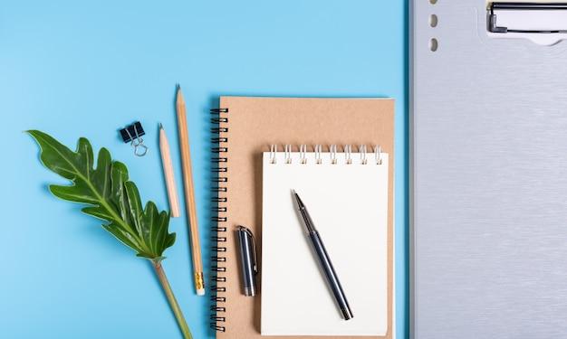 Trabalha a composição do ritmo com arquivo de documento, caderno, caneta, lápis e folhas verdes, vista superior