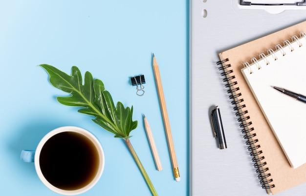 Trabalha a composição do ritmo com uma xícara de café, arquivo de documento, caderno, caneta, lápis e folhas verdes, vista superior