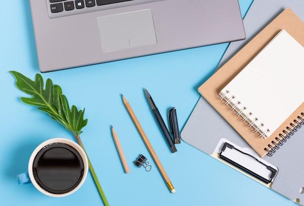 Trabalha a composição do ritmo com uma xícara de café, arquivo de documento, notebook, laptop e folhas verdes, vista superior