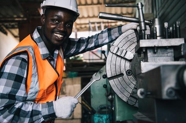 Trabalhador africano americano com óculos de segurança e máquina de controle de torno para furar componentes com uma chave inglesa