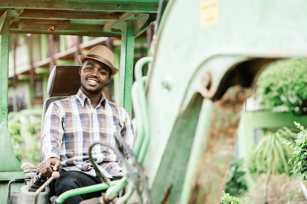 Trabalhador africano dirigindo retroescavadeira de equipamentos de construção pesada com sorriso e felicidade