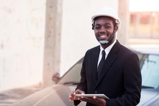 Trabalhador africano engenheiro de construção em pé e usar teblet com o carro