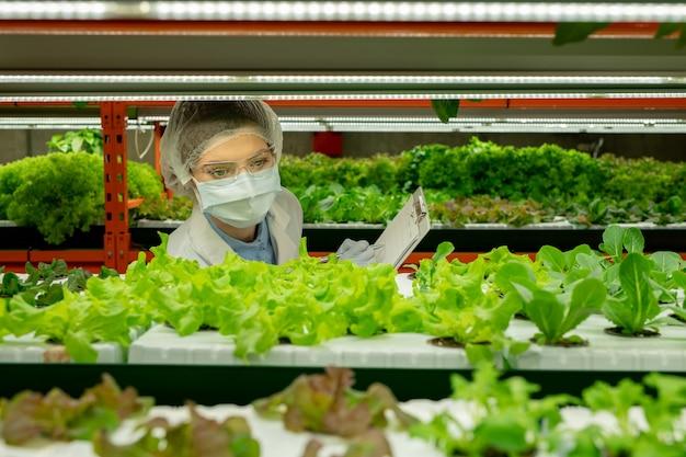 Trabalhador agrícola vertical ocupado com óculos de segurança, boné descartável e máscara fazendo anotações na prancheta enquanto controla o crescimento de mudas
