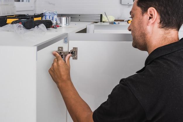 Trabalhador ajustando as dobradiças de um armário de cozinha
