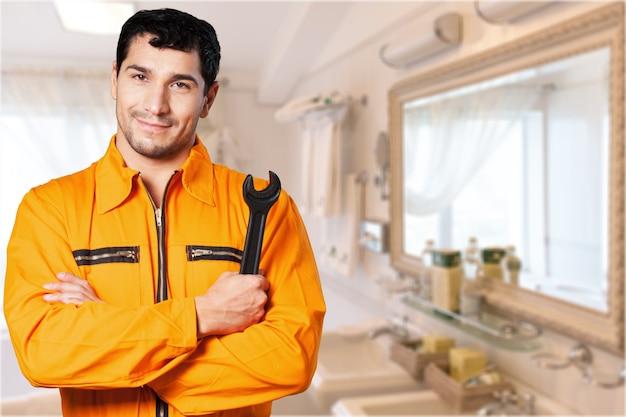 Trabalhador alegre segurando a chave no fundo da cozinha, encanador de homem.