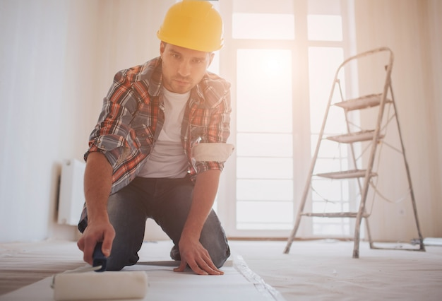 Trabalhador anexando papel de parede. o construtor coloca cola no papel de parede