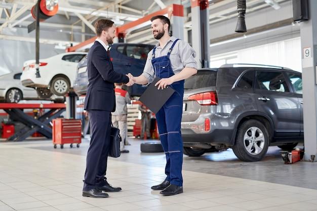 Trabalhador, apertando as mãos com o cliente na loja de serviço de carro