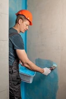 Trabalhador aplicando tinta impermeabilizante na parede do banheiro Foto Premium