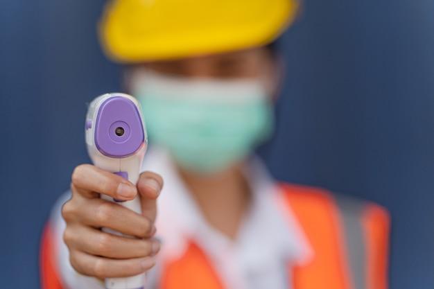 Trabalhador asiático com máscara facial usando termômetro infravermelho sem contato