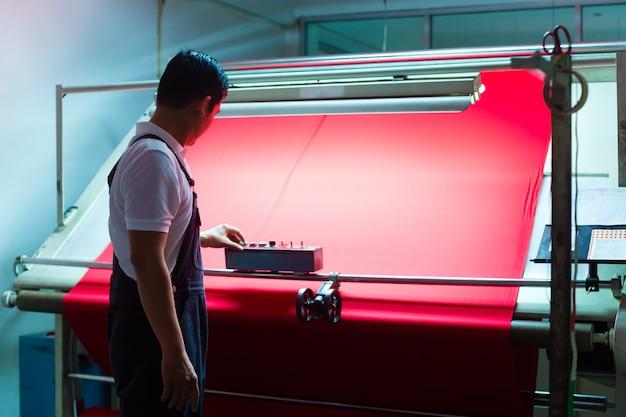 Trabalhador asiático controla tecidos na fábrica têxtil