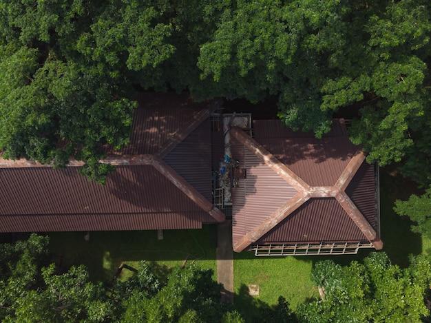 Trabalhador asiático fixação edifício telhado