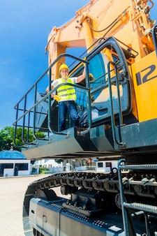 Trabalhador asiático no local de construção de escavadeira de pá