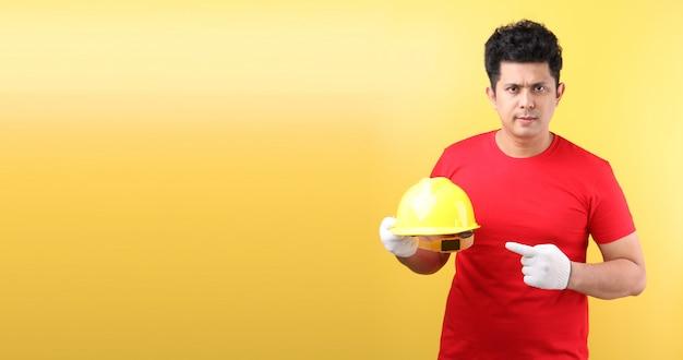 Trabalhador asiático ou coordenador da indústria do homem que trabalham um arquiteto na parede amarela, dia labour internacional do conceito.