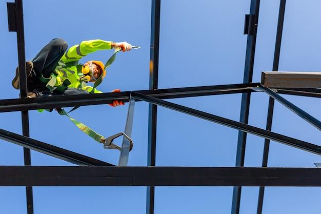 Trabalhador asiático usa equipamento de segurança de altura para instalar o telhado no canteiro de obras ;. dispositivo antiqueda para trabalhador com ganchos para cinto de segurança.
