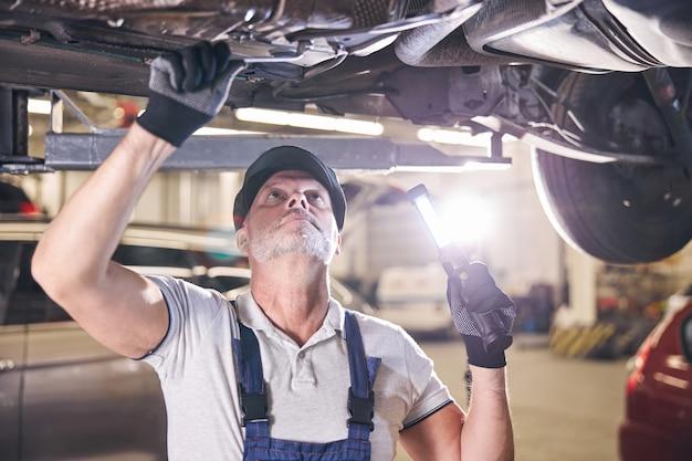 Trabalhador barbudo consertando carro em oficina mecânica