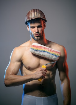 Trabalhador bonito com rolo de pintura pintor homem musculoso pintor homem segurando rolo de pintura profissional