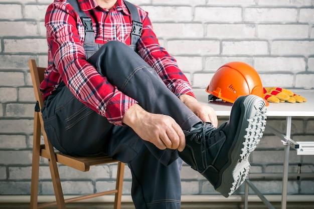 Trabalhador calçar botas de trabalho no vestiário em uma fábrica. construção de segurança.