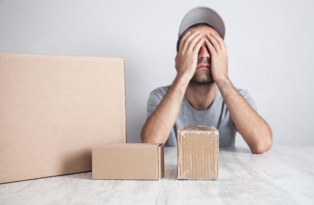Trabalhador cansado com uma caixa de papelão. produtos, comércio, varejo, entrega