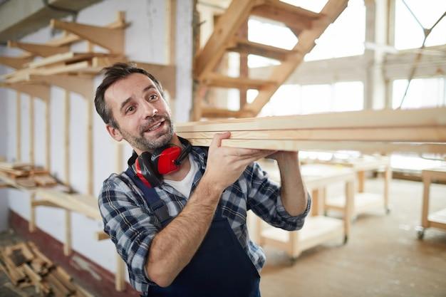 Trabalhador carregando tábuas de madeira