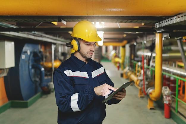 Trabalhador caucasiano em traje de proteção, capacete e antifones nas orelhas usando o tablet para o trabalho em pé na planta da indústria pesada.