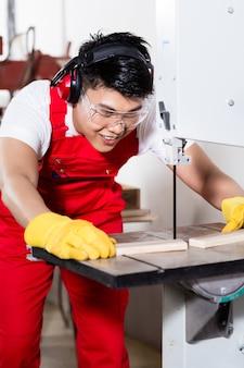 Trabalhador chinês em serra em fábrica industrial cortando uma peça de trabalho
